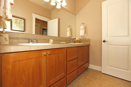 Beige bathroom with nice cabinets and open door Stock Photo - 12312419