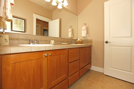 Beige bathroom with nice cabinets and open door Stock Photo - 12312419