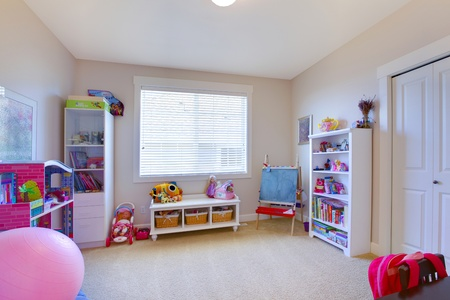 Girl play game room in white and pink with lots of toys photo