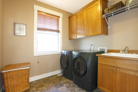 Laundry room with black appliances and nice cabinets photo