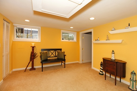 Yellow room in the basement with bench.