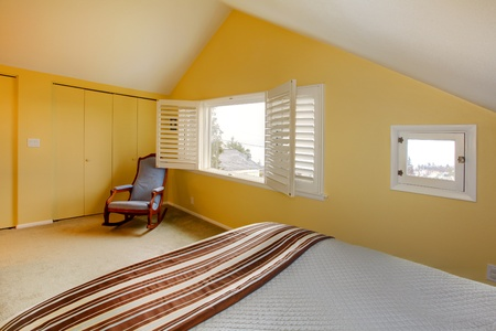 Yellow attic room with chair and bed. photo