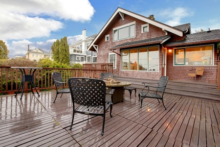 Browns house with large deck and outdoor furniture.