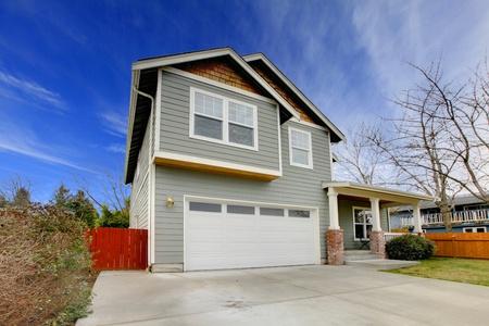 Grijze huis met rode hek.