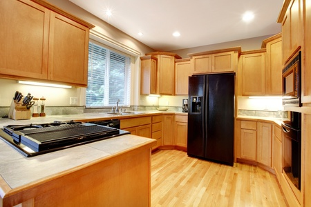 Kitchen with wood cabinets and black refrigirator. photo