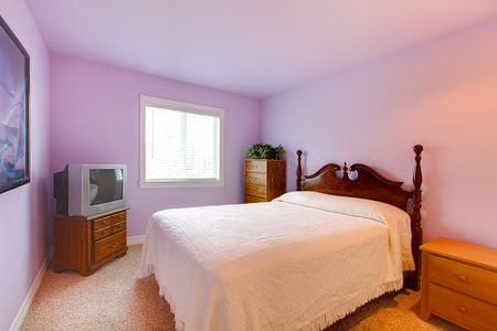 nightstand: Bedroom with purple walls and white bed.