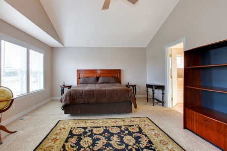 Large bedroom with brown bed. photo