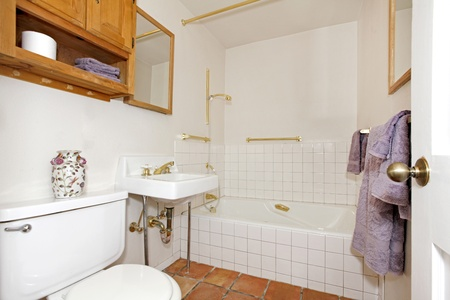 Simple white bathroom with purple towels. photo