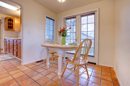 country house style: Dining room table with tile and french door.