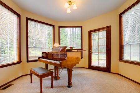 피아노와 윈도우의 제비를 가진 둥근 방.
