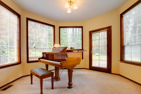 Round room with piano and lots of windows. Stock Photo
