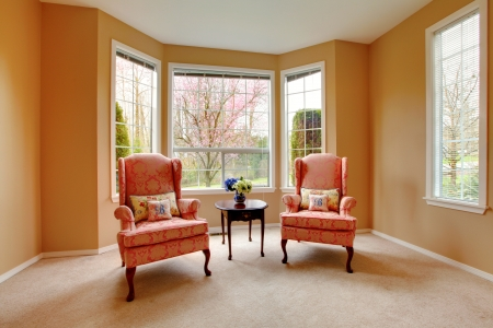 Elegant living room with two pink arm chairs. photo