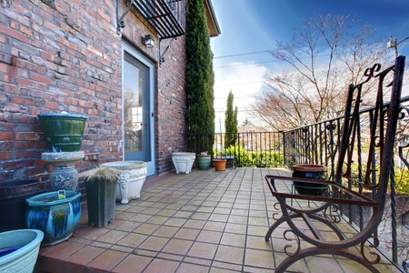 English brick hose deck with pots and iron chairs photo
