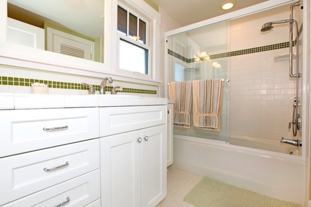 Green bathroom with tub and white cabinets Stock Photo - 12311964