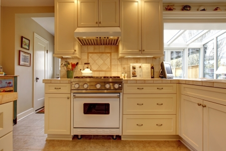 kitchen cabinets: Yellow white kitchen with large stove