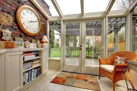 designer: Garden room wall with clock and book shelves Stock Photo