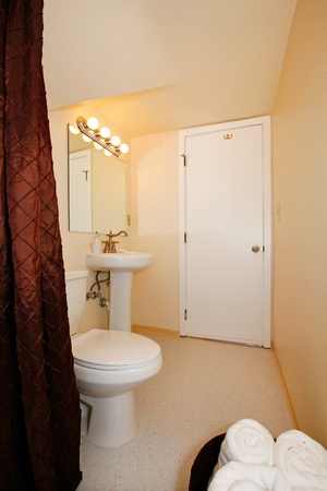 Small yellow bathroom with white towels. photo