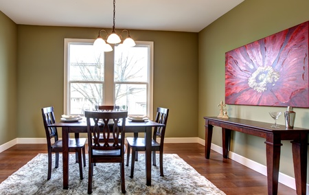 Beautiful and nice dining room with green walls and red paainting. photo
