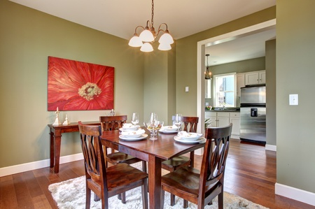 dining room: Beautiful green dining room with kitchen view. Stock Photo