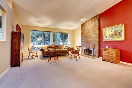 Large living room with red wall and brick fireplace. Stock Photo - 12621120