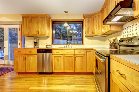 appliances: Golden orange kitchen with hardwood floor. Stock Photo