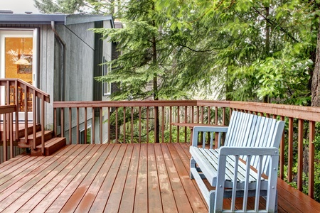 porch: Small deck with blue chair and grey house. Stock Photo
