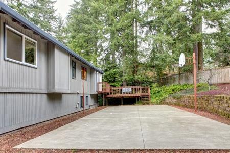 Grey house with backyard with basket ball area. Stock Photo - 12621196
