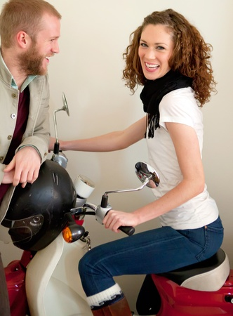 Beautiful female model on the scooter with flirting guy  photo