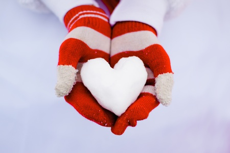 Romantic white snow and red gloves holding it