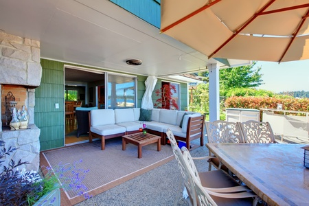 beach front: House exterior covered living room with sofa and table.