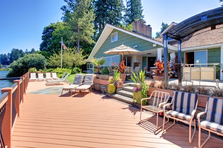 Great large brown new deck with lake front green house. Stock Photo - 12621303