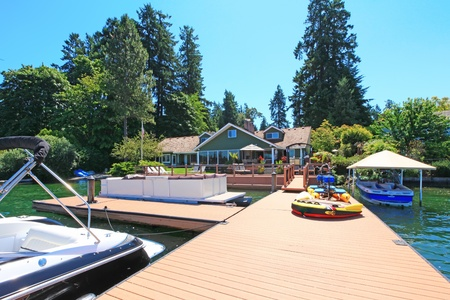 Beautiful lake waterfront property with dock and very large deck with many water boats and toys. Stock Photo - 12621293