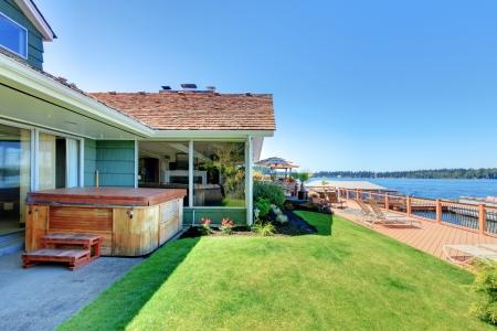 Een verhaal groene huis met bad en groot bad met een dek en het meer.