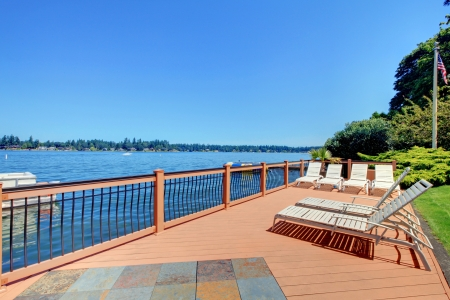 waterfront property: Beautiful large deck near the lake with  chairs and landscape. Stock Photo