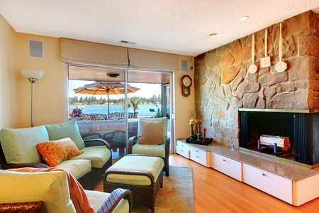 Large fireplace living room with lake view and sofa.