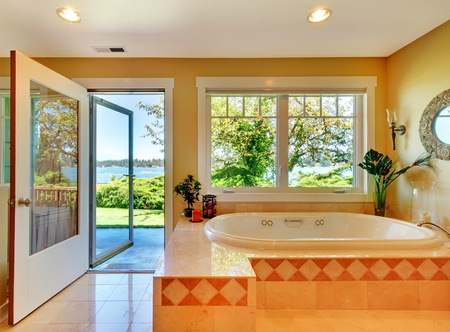Large yellow bathroom with tub and lake view and open door. photo