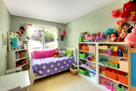 Kids bedroom with green walls and purple bed and may toys.