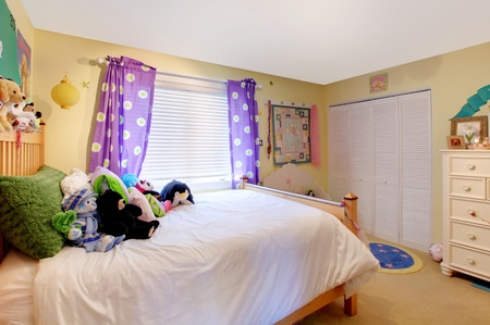 Yelow baby room with purple curtains and yellow walls. Stock Photo