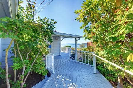 Grey house front door exterior with wood deck walkway and water view. photo