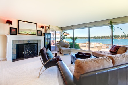 Living room with fireplace, modern furniture and water view with large windows. photo