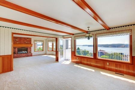 Large living woom with water view and wood beams and beige carpet. photo