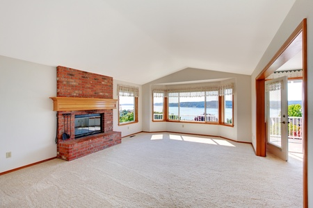 Bright large living room with brick fireplace and water view. photo