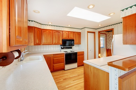 Bright large kitchen with skylight, water view and honey warm cabinet color.  photo
