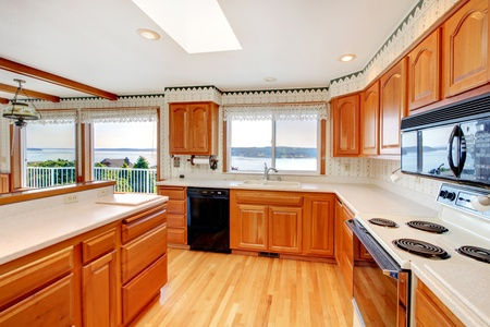 black appliances: Bright large kitchen with skylight, water view and honey warm cabinet color.