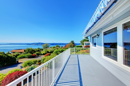front of: Front door porch with water view and grey house and bright sunny light.