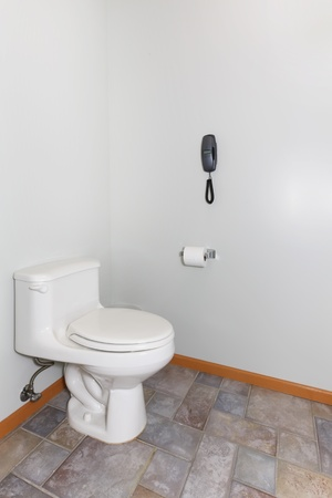 Soimple toilet with tile floor and grey walls. Stock Photo - 12621205