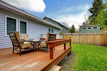 Simlle small grey house deck with outdoor furniture and fenced back yard.