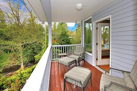 Balcony House buitenkant met tuinmeubilair en uitzicht op bossen en de rivier.
