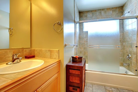 Bathroom with tub behind modern glass, stone tile, and white sink in a wood cabinet. photo