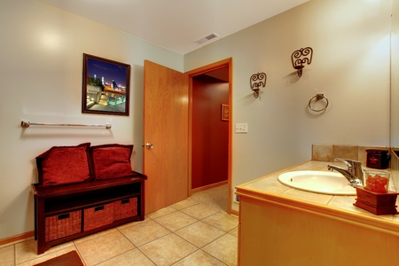 Nice large bathroom with simple classic design and bench with red pillows. photo